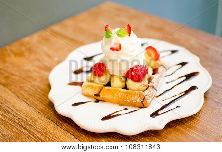 Waffle With Ice Cream Topping With Strawberry And Banana On Wooden Table