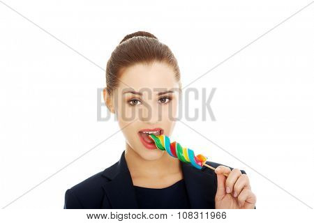Young happy businesswoman licking a lolipop