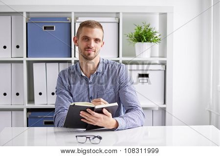 Businessman Sitting In Office And Writing Daily Plan In His Diary