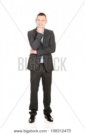 Confident young businessman with hand under chin