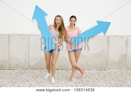 Teenage students holding blue arrows and pointing in diferent directions
