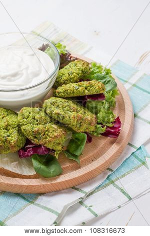 Falafel and sour cream, wood background