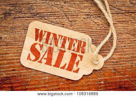 winter sale sign - red stencil text on a paper price tag against grunge wood