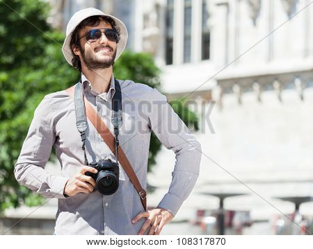 Smiling young tourist holding his digital camera