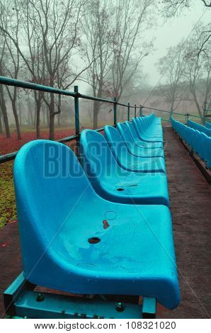 Rows Of Blue Plastic Seats In The Autumn Park In Foggy Weather