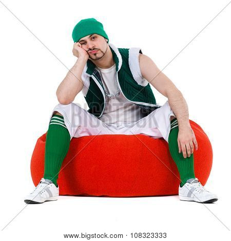 Melancholy man dressed like a gnome sitting on red bag with gifts, isolated over white