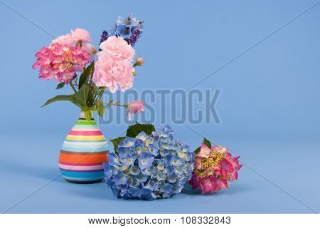 Hydrangeas pink and blue and other flowers in vase on colorful background