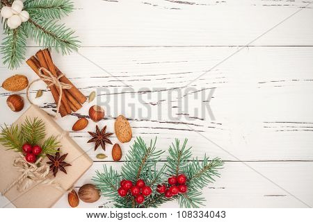 Christmas background with presents fir branches and spices on the old wooden board with copy space