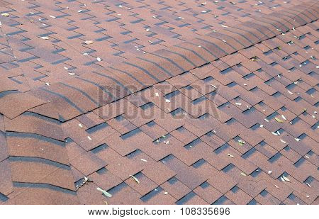 Top View Of Brown Roof Shingles With A Few Fallen Leaves