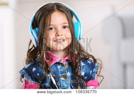 Little girl with headphones in the room, close up