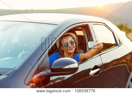 Woman In Hat And Sunglasses Making Self Portrait Sitting In The Car