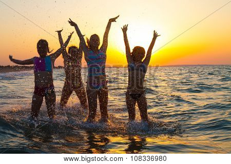 Group of happy young girls jumping at the beach