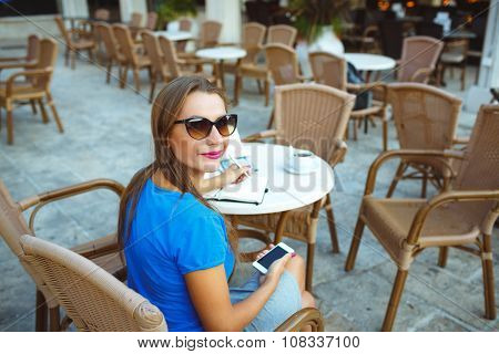 Young Pretty Modern Blogger Using Smartphone And Makes Notes In A Notebook In A Cafe