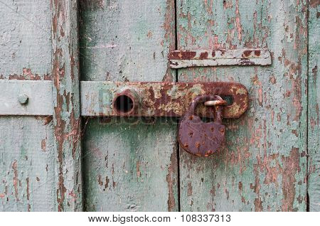 Detail Of Old Wooden Door With Rusty Padlock