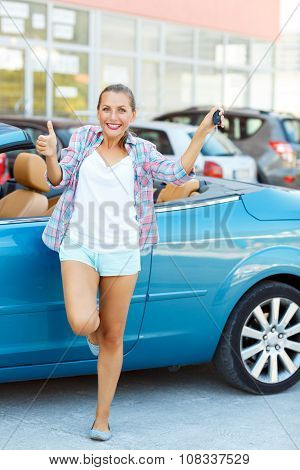 Young Happy Woman Standing Near A Convertible With The Keys In His Hand And Thumb Up