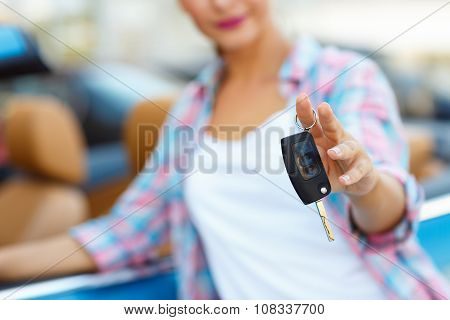 Young Woman Standing Near A Convertible With Keys In Hand