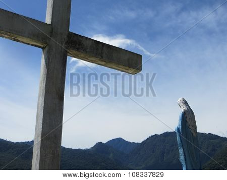 Cross and Mary in front of mountains