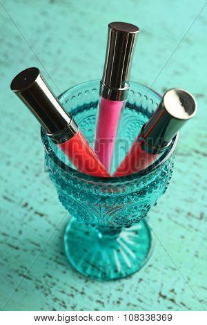 Make up lipsticks on wooden table closeup