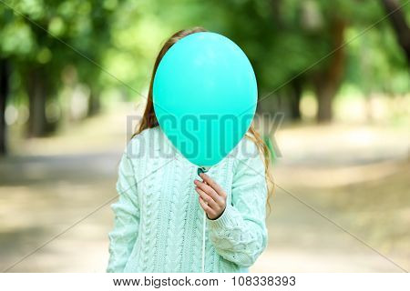 Girl holding balloon near face