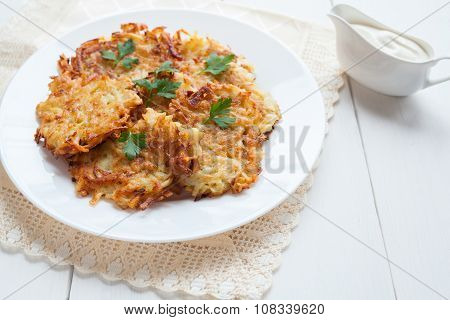 Potato pancaces or latke traditional Hanukkah celebration food with sour cream on white rustic backg