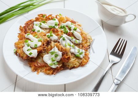 Homemade fried potato pancakes or latke traditiona Hanukkah celebration food with greens and sour cr