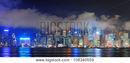 Hong Kong skyline at night with clouds over Victoria Harbour.