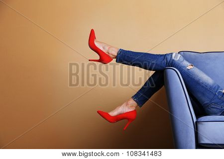 Woman legs on sofa with stylish shoes in room