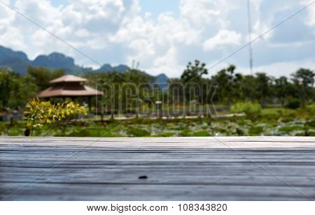 Wood Floor With Pond And Garden Background