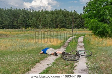Man lying on a country road after he fallen down from an ancient bicycle