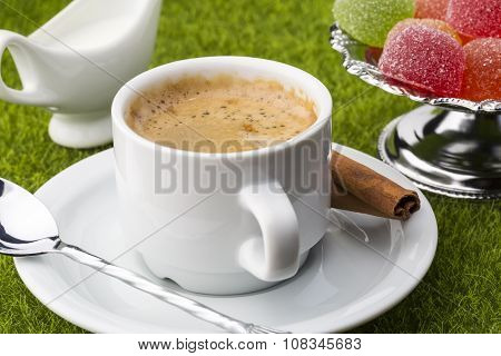 White cup of fresh coffe with dessert