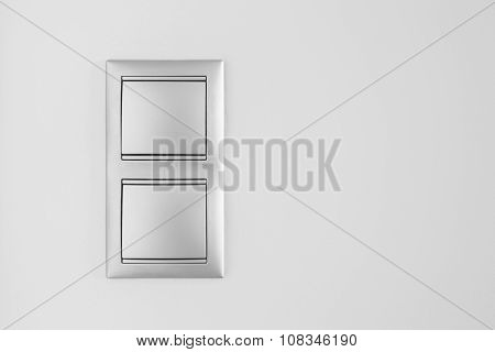 Double Metallic Light Switch Over A White Wall. Copy Space