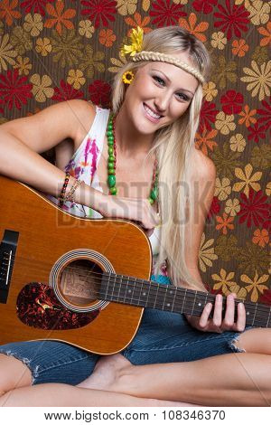 Blond smiling hippie girl playing guitar
