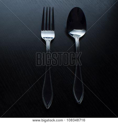 fork and spoon on a black table