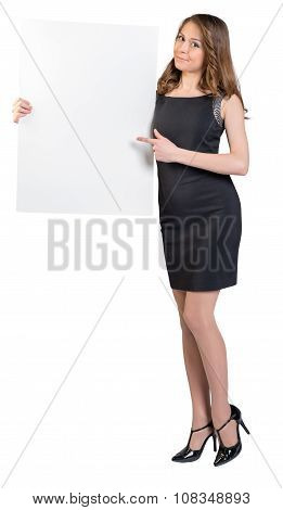 Young girl is holding a big empty billboard, shows forefinger on him