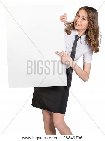 Woman looks out from behind large blank poster showing forefinger on him