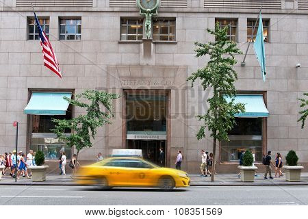 NEW YORK - SEPTEMBER 06: Yellow Taxi Cab Speeding Past Entrance to Tiffany and Company Luxury Jewellery Retail Store on Street Busy with Pedestrians in New York City, New York, USA. September 06 2015.