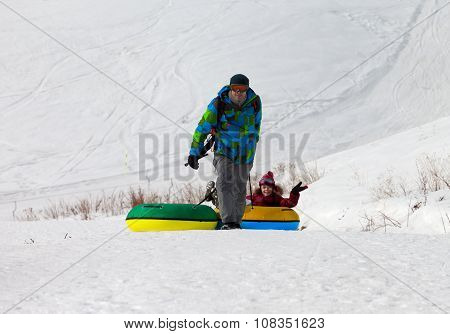 Father And Daughter With Snow Tube