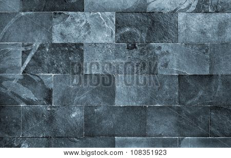 Fraction of a dark schist wall with brick texture