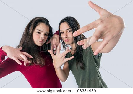 Cool teenager girl friends in happy expression doing hand signs