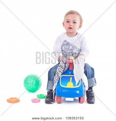 Young boy riding a toy car