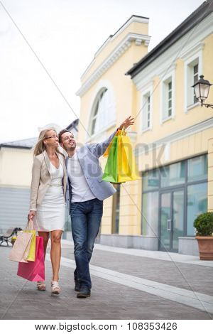 Smiling couple with bags in outlet