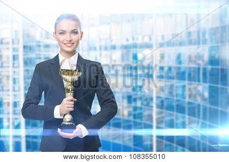 Portrait of businesswoman keeping gold cup, blue background. Concept of victory and success