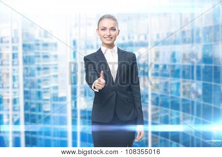 Portrait of business woman who thumbs up, blue background. Concept of leadership and success