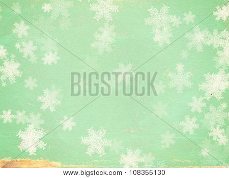 Grunge Christmas background of green color with snowflakes and paper texture