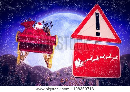 Christmas road sign against christmas village under full moon