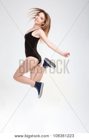 Young carefree beautiful joyful girl in black leotard and sneakers enjoying jumping