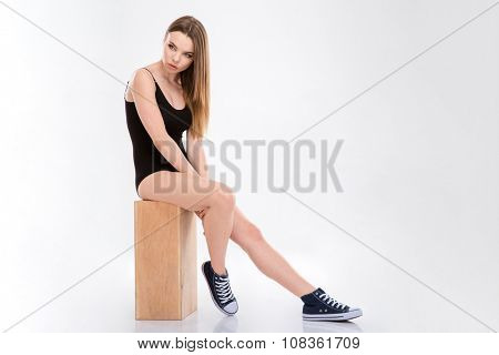 Sensual pensive natural young woman in black swimsuit and sneackers sitting on wooden box