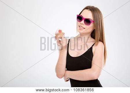 Beautiful smiling happy content joyful attractive girl in pink sunglasses holding a cupcake in her hands