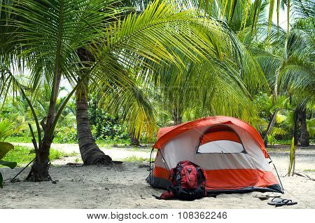 White-orange Summer Tent, Red Backpack And Slippers In Coconut Palm Tree Forest Next To Sandy Beach