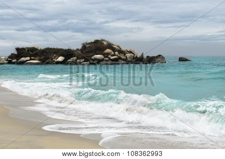 Tiny Rocky Isle Close To Sandy Beach And Foamy Waves In Turquoise Sea